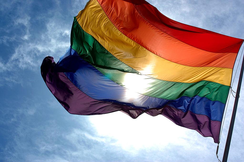 1024px-Rainbow_flag_and_blue_skies
